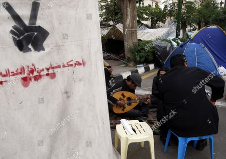 An Egyptian Protester Plays the Oud Instrument As He Sits Next to the Six April Movement Tent During the Continuing Sit-in at the Parliament and Prime Minister Office Street One Day Before the Run-off in the First Round of the Parliamentary Elections at the Parliament Gate in Cairo Egypt 04 December 2011 According to Media Reports the Decision on the New Egyptian Cabinet was Delayed Again on 03 December After Prime Minister-designate Kamal Al-ganzouri Said He Would Reconsider Some of the Nominations Many Activists Have Rejected Al-ganzouri Because of His Ties to the Mubarak Regime He Served As Prime Minister From 1996-1999 the Interim Ruling Supreme Council of the Armed Forces Appointed Al-ganzouri to Replace Outgoing Premier Essam Sharaf who Resigned After After 42 People Were Killed in Countrywide Clashes Between Protesters and Police in November the Clashes Were the Worst Since the January 25 Revolution Which Led to the Fall of Mubarak Egypt Has Seen Renewed Protests with Activists Pushing For the Military to Speed Up the Transfer of Power to a Civilian Government Egypt Cairo