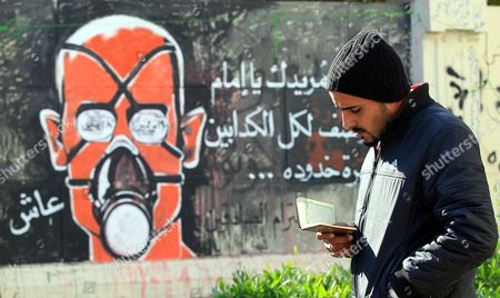Stock Photo of An Egyptian Protester Reads From the Koran As He Stands Next to Graffiti During a Sit-in Outside Prime Minister's Office in Cairo Egypt 12 December 2011 Reports State That Some Political Groups Had Moved Their Sit-in From Tahrir Square to Outside the Cabinet Building on Qasr Al-aini Street to Protest Against the New Prime Minister Kamal Ganzouri Protesters Have Forced Ganzouri to Hold Governmental Meetings Away From the Cabinet Building Since the New Government was Sworn-in on 07 December Egypt Cairo
