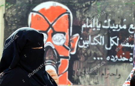 An Egyptian Woman Walks Next to Graffiti During a Sit-in Outside Prime Minister's Office in Cairo Egypt 12 December 2011 Reports State That Some Political Groups Had Moved Their Sit-in From Tahrir Square to Outside the Cabinet Building on Qasr Al-aini Street to Protest Against the New Prime Minister Kamal Ganzouri Protesters Have Forced Ganzouri to Hold Governmental Meetings Away From the Cabinet Building Since the New Government was Sworn-in on 07 December Egypt Cairo