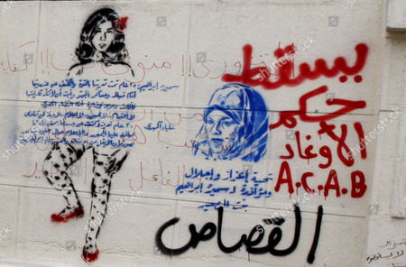 Graffitis Depicting Activist Samira Ibrahim who Accused the Military of Having Made Her Go Though Virginity Tests Following Her Arrest (r) and Alia Mahdi (l) who Posted an Image of Herself Naked on Internet 'To Challenge the Retsrictions on Liberty' As Seen on a Wall in Parliament and Prime Minister Office Street While Some Protesters Continue Their Sit-in There and in Neraby Tahrir Square One Day Before the Run-off in the First Round of the Parliamentary Elections Cairo Egypt 04 December 2011 According to Media Reports the Decision on the New Egyptian Cabinet was Delayed Again on 03 December After Prime Minister-designate Kamal Al-ganzouri Said He Would Reconsider Some of the Nominations Many Activists Have Rejected Al-ganzouri Because of His Ties to the Mubarak Regime He Served As Prime Minister From 1996-1999 the Interim Ruling Supreme Council of the Armed Forces Appointed Al-ganzouri to Replace Outgoing Premier Essam Sharaf who Resigned After After 42 People Were Killed in Countrywide Clashes Between Protesters and Police in November the Clashes Were the Worst Since the January 25 Revolution Which Led to the Fall of Mubarak Egypt Has Seen Renewed Protests with Activists Pushing For the Military to Speed Up the Transfer of Power to a Civilian Government Egypt Cairo