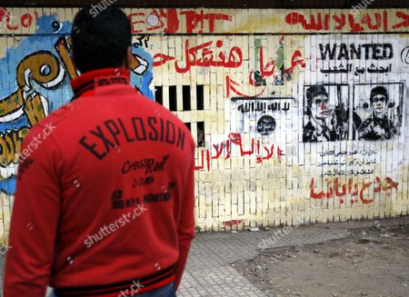 Stock Image of An Egyptian Youth Looks at Grafittis One at Left Depicts a Soldier Accused of Having Fired at Protesters at Eye/head Level During Clashes Weeks Eralier As Some Protesters Continue Their Sit-i in Tahrir Square One Day Before the Run-off in the First Round of the Parliamentary Elections Cairo Egypt 04 December 2011 According to Media Reports the Decision on the New Egyptian Cabinet was Delayed Again on 03 December After Prime Minister-designate Kamal Al-ganzouri Said He Would Reconsider Some of the Nominations Many Activists Have Rejected Al-ganzouri Because of His Ties to the Mubarak Regime He Served As Prime Minister From 1996-1999 the Interim Ruling Supreme Council of the Armed Forces Appointed Al-ganzouri to Replace Outgoing Premier Essam Sharaf who Resigned After After 42 People Were Killed in Countrywide Clashes Between Protesters and Police in November the Clashes Were the Worst Since the January 25 Revolution Which Led to the Fall of Mubarak Egypt Has Seen Renewed Protests with Activists Pushing For the Military to Speed Up the Transfer of Power to a Civilian Government Egypt Cairo