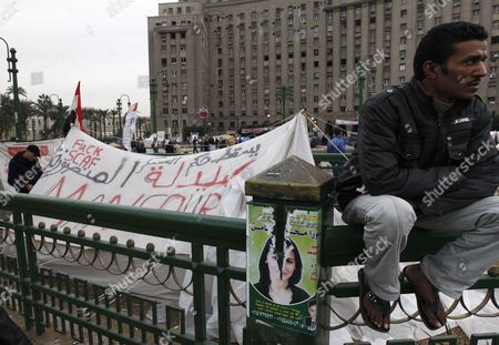 Stock Photo of An Egyptian Sits Next to a Protesters Tent Whith Slogans Against the Ruling Military Council Written on It As Some Protesters Continue Their Sit-i in Tahrir Square One Day Before the Run-off in the First Round of the Parliamentary Elections in Cairo Egypt 04 December 2011 According to Media Reports the Decision on the New Egyptian Cabinet was Delayed Again on 03 December After Prime Minister-designate Kamal Al-ganzouri Said He Would Reconsider Some of the Nominations Many Activists Have Rejected Al-ganzouri Because of His Ties to the Mubarak Regime He Served As Prime Minister From 1996-1999 the Interim Ruling Supreme Council of the Armed Forces Appointed Al-ganzouri to Replace Outgoing Premier Essam Sharaf who Resigned After After 42 People Were Killed in Countrywide Clashes Between Protesters and Police in November the Clashes Were the Worst Since the January 25 Revolution Which Led to the Fall of Mubarak Egypt Has Seen Renewed Protests with Activists Pushing For the Military to Speed Up the Transfer of Power to a Civilian Government Egypt Cairo