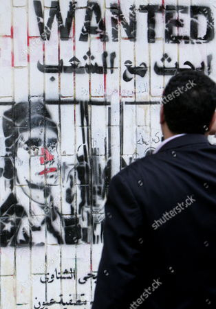 Stock Picture of An Egyptian Looks at a Wanted Grafitti Depicting a Soldier Accused of Having Fired at Protesters at Eye/head Level During Clashes Weeks Eralier As Some Protesters Continue Their Sit-i in Tahrir Square One Day Before the Run-off in the First Round of the Parliamentary Elections Cairo Egypt 04 December 2011 According to Media Reports the Decision on the New Egyptian Cabinet was Delayed Again on 03 December After Prime Minister-designate Kamal Al-ganzouri Said He Would Reconsider Some of the Nominations Many Activists Have Rejected Al-ganzouri Because of His Ties to the Mubarak Regime He Served As Prime Minister From 1996-1999 the Interim Ruling Supreme Council of the Armed Forces Appointed Al-ganzouri to Replace Outgoing Premier Essam Sharaf who Resigned After After 42 People Were Killed in Countrywide Clashes Between Protesters and Police in November the Clashes Were the Worst Since the January 25 Revolution Which Led to the Fall of Mubarak Egypt Has Seen Renewed Protests with Activists Pushing For the Military to Speed Up the Transfer of Power to a Civilian Government Egypt Cairo