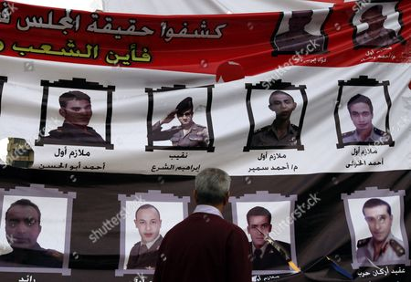 An Egyptian Man Looks at a Banner Depicting Army Officers As Some Protesters Continue Their Sit-i in Tahrir Square One Day Before the Run-off in the First Round of the Parliamentary Elections in Cairo Egypt 04 December 2011 According to Media Reports the Decision on the New Egyptian Cabinet was Delayed Again on 03 December After Prime Minister-designate Kamal Al-ganzouri Said He Would Reconsider Some of the Nominations Many Activists Have Rejected Al-ganzouri Because of His Ties to the Mubarak Regime He Served As Prime Minister From 1996-1999 the Interim Ruling Supreme Council of the Armed Forces Appointed Al-ganzouri to Replace Outgoing Premier Essam Sharaf who Resigned After After 42 People Were Killed in Countrywide Clashes Between Protesters and Police in November the Clashes Were the Worst Since the January 25 Revolution Which Led to the Fall of Mubarak Egypt Has Seen Renewed Protests with Activists Pushing For the Military to Speed Up the Transfer of Power to a Civilian Government Egypt Cairo