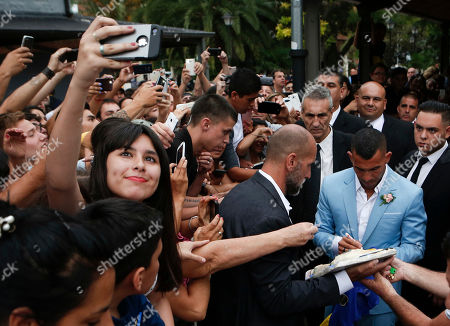 Stock Picture of Soccer star Carlos Tevez, right, signs autographs after getting married to Vanesa Mansilla after the church ceremony in Buenos Aires, Argentina