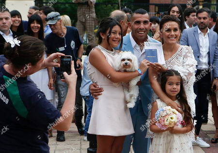 Soccer star Carlos Tevez and his wife Vanesa Mansilla, right, pose for photos after getting married outside the church in Buenos Aires, Argentina