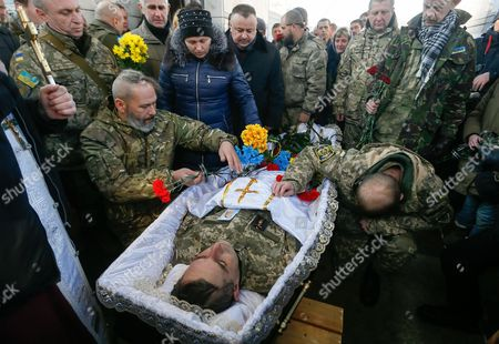 Comrades and relatives react during the funeral ceremony for the 'Kievskaya Rus' battalion serviceman Volodymyr Andreshkiv who was killed in the eastern Ukraine conflict at the Independence Square in Kiev, Ukraine, 22 December 2016. Secretary of the National Security and Defense Council of Ukraine Oleksandr Turchynov has announced that during recent battles near the town of Svitlodarsk the Armed Forces of Ukraine counter-attacked enemy troops, moved forward and took new positions as UNIAN agency report.