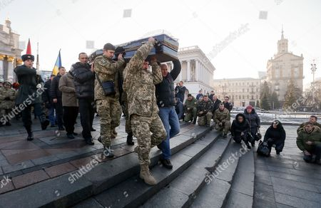Stock Picture of Ukrainians carry coffin with the body of the 'Kievskaya Rus' battalion serviceman Volodymyr Andreshkiv who was killed in the eastern Ukraine conflict, during the funeral ceremony at the Independence Square in Kiev, Ukraine, 22 December 2016. Secretary of the National Security and Defense Council of Ukraine Oleksandr Turchynov has announced that during recent battles near the town of Svitlodarsk the Armed Forces of Ukraine counter-attacked enemy troops, moved forward and took new positions as UNIAN agency report.