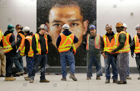Construction workers stand in front of a mosaic by Chuck Close at the new 86th Street subway station in New York,. The first phase of the 2nd Avenue subway line, which has three stops, is scheduled to open on Jan. 1, 2017