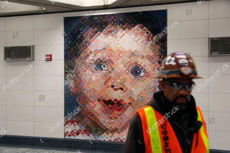 A construction worker walks past a Chuck Close mosaic in the new 86th Street subway station in New York,. The first phase of the 2nd Avenue subway line, which has three stops, is scheduled to open on Jan. 1, 2017