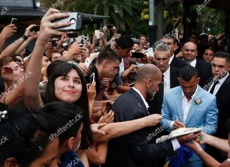 A fan takes a selfie as soccer idol Carlos Tevez signs autographs outside the church where he married Vanesa Mansilla in Buenos Aires, Argentina. The Boca Juniors player is negotiating his transfer to China's Shanghai Shenhua team