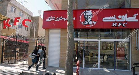 Iranian Women Pass in Front of the Kfc Restaurant in the City of Karaj in the Alborz Province in Central Iran 27 February 2012 the American Fast Food Chain Restaurant Kentucky Fried Chicken Has Opened a Branch in Iran Despite Harsh Us Sanctions Against Iran Over That Country's Nuclear Programmes Iranian Media Reported on 25 February Amir-hossein Alizadeh the Licence Holder Said It Took Him Five Years to Get the Permission From Relevant Local Authorities to Re-open Kfc in Iran Kfc was Closed in Iran Following the 1979 Islamic Revolution Due to Its Affiliation with the Us the Country's Political Arch-enemy Iran (islamic Republic Of) Karaj
