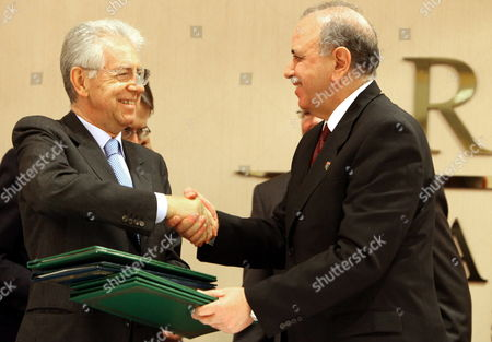 Libya's Prime Minister Abdurrahim El-keib (r) and Italian Prime Minister Mario Monti (l) ) Shake Hands and Exchange Documents of a Joint Cooperation Agreement in Tripoli Libya 21 January 2012 Monti is in Tripoli to Revive a Treaty of Frienship with Libya Following the Fall of Muammar Gaddafi Regime Libyan Arab Jamahiriya Tripoli