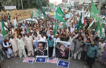 Stock Image of People Carry Posters Designed on Computer Featuring Us President Barack Obama (l) and Us Secretary of State Hillary Clinton During a Protest Against the Nato Airstrikes on Pakistani Military Checkposts in Mohmand Tribal Agency in Karachi Pakistan 01 December 2011 Pakistan Said on 29 November It Would Boycott an International Conference on Afghanistan in Bonn Germany Next Month in Protest of the Nato Attack on Pakistani Army Posts That Killed 24 Soldiers and Sparked Anti-western Protests in the Country the Government Made the Decision at a Cabinet Meeting in the Eastern City of Lahore Chaired by Prime Minister Yousuf Raza Gilani Pakistan Karachi