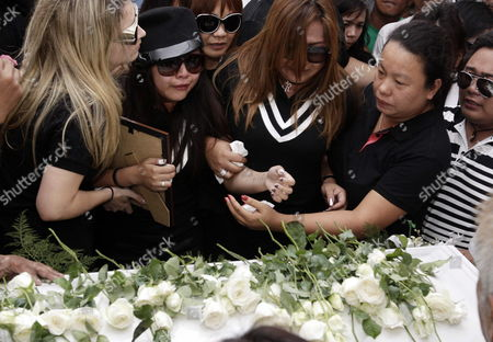 Filipino Singer/actress Charice Pempengco (2-l) Weeps Next to Her Mother Raquel (3-l) After Paying Her Last Respect to Her Father Ricky Pempengco During a Burial Ceremony at a Cemetery in Cabuyao Laguna Province South of Manila Philippines 05 November 2011 the Father of the 18-year-old Glee Star was Laid to Rest Five Days After He was Stabbed to Death by Construction Worker Angel Capili Jr Hundreds of Fans Converged on the Cemetery to Get a Glimpse of the Singer Officials Said Philippines Manila