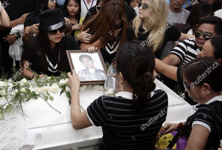 Filipino Singer/actress Charice Pempengco (l) Holds Her Father Ricky Pempengco Portrait During a Burial Ceremony at a Cemetery in Cabuyao Laguna Province South of Manila Philippines 05 November 2011 the Father of the 18-year-old Glee Star was Laid to Rest Five Days After He was Stabbed to Death by Construction Worker Angel Capili Jr Hundreds of Fans Converged on the Cemetery to Get a Glimpse of the Singer Officials Said Philippines Manila