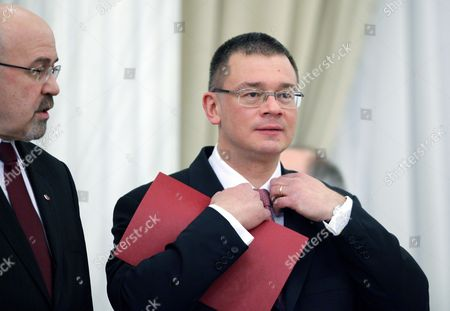 Romanian New Prime Minister Mihai Razvan Ungureanu (r) Adjusts His Suit As Being Watched by His Vice-premier Marko Bella (l) During the Swearing in Ceremony at the Presidential Palace in Bucharest Romania 09 February 2012 Mihai Razvan Ungureanu Former Head of Romanian Foreign Intelligence Service (sie) Named His Cabinet on 08 February Replacing Almost All Ruling Party Ministers in an Attempt to Make a Clean Break From His Predecessor Emil Boc who Quit Due to a Series of Protests Against Austerity Measures Romania Bucharest