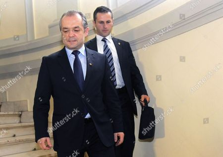 Romanian Prime Minister Emil Boc (l) Escorted by a Bodyguard (r) Looks Leaves Democrat-liberal Party (pdl) Headquarters Shortly After He Resigned in Bucharest Romania 06 February 2012 Emil Boc Announced During the Last Government Working Session That He and His Entire Cabinet Team is Resigning Romania Bucharest
