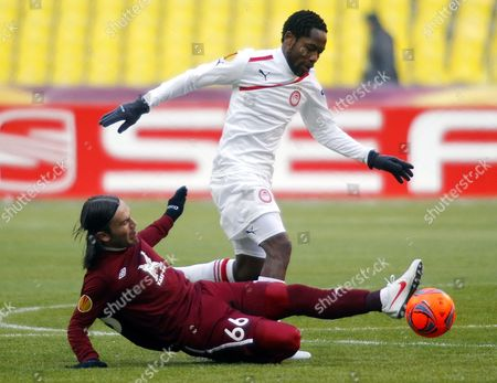 Bebars Natcho (bottom) of Rubin Kazan Tackles Jean Makoun (up) of Olympiakos Piraeus During Their Uefa Europa League Round of 32 Soccer Match in Moscow Russia 14 February 2012 Russian Federation Moscow