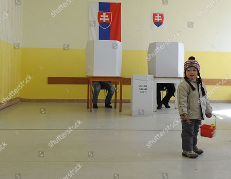 A Boy Waits For His Father to Finish Preparing His Ballot at a Polling Station in Bratislava Slovakia During Early Elections on 10 March 2012 Slovakian Parliamentary Elections Began Saturday in a Climate of Public Anger Over Corruption Allegations Against Politicians Media Reports State That Opinion Polls See Former Prime Minister Robert Fico's Smer Social Democrats Poised to Heavily Defeat the Center-right Sdku Party's Outgoing Prime Minister Iveta Radicova Slovakia (slovak Republic) Bratislava