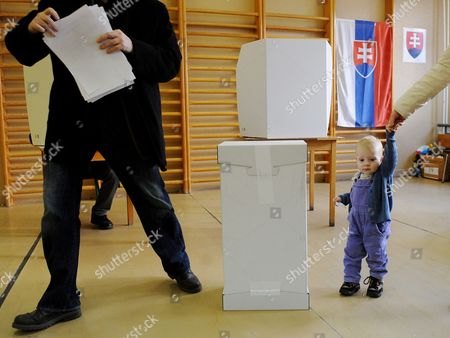 A Boy Waits For His Father to Finish Preparing His Ballot at a Polling Station in Bratislava Slovakia 10 March 2012 During Early Elections Slovakian Parliamentary Elections Began Saturday in a Climate of Public Anger Over Corruption Allegations Against Politicians Media Reports State That Opinion Polls See Former Prime Minister Robert Fico's Smer Social Democrats Poised to Heavily Defeat the Center-right Sdku Party's Outgoing Prime Minister Iveta Radicova Slovakia (slovak Republic) Bratislava