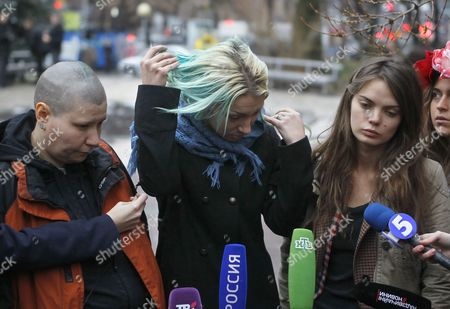 Member of a Ukrainian-based Feminist Group Femen Inna Shevchenko (c) Shows Her Painted by Green Antiseptic and Cut Hair As Her Colleges Aleksandra Nemchinova (l) and Oksana Shachko (r) Stand Near During Their Talk with Journalists in Kiev Ukraine 21 December 2011 They Were Arrested in the Belarusian Capital Minsk on Tuesday 19 December After Disrobing and Displaying Language Insulting to Belarusian President Aleksandr Lukashenko Written on Their Torsos the Demonstration Took Place in Front of the Headquarters of the Belarusian National Secret Police the Kgb Belarus' Belapan News Agency Reported Members of a Ukrainian Feminist Group Accused Belarusian Kgb (secret Police) of Abducting and Physically Abusing Them Because They Took Their Clothes Off in Public to Make a Political Point Belarusian Law Enforcement Officers Released the Three Ukrainian Women on Tuesday Evening in a Forest Near the City Gomel Some 300 Kilometres From Minsk After Making Physical Threats Against Them and Forcing Them to Undress Said Femen Member Aleksandra Shevchenko in a Twitter Comment Temperatures in the Region at the Time of Their Release on Tuesday Evening Were Approximately Zero Degrees Centigrade According to Recent Weather Reports Local Villagers Assisted the Ukrainian Women in Contacting Their Country's Embassy Which Sent a Worker to Escort Them Back to Ukraine the Ukrainian Interfax News Agency Reported Ukraine Kiev