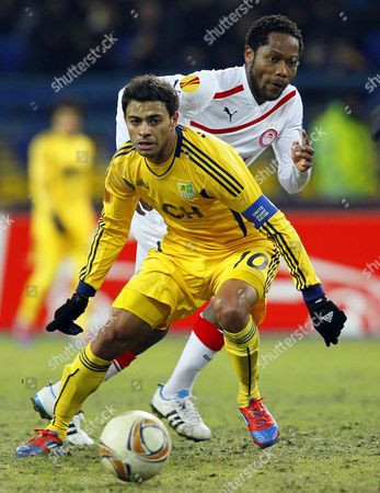 Cleiton Xavier (front) of Metalist Kharkiv Vies For the Ball with Jean Makoun (back) of Olympiacos Piraeus During Their Uefa Europa League Round of 16 First Leg Soccer Match in Kharkiv Ukraine 08 March 2012 Ukraine Kharkiv