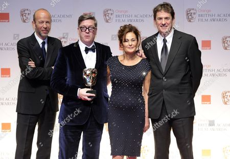 (l-r) British Producer Eric Fellner Swedish Director Tomas Alfredson South African Producer Robyn Slovo and New Zealand Producer Tim Bevan Pose with the Outstanding British Movie Award For Their Movie 'Tinker Tailor Soldier Spy' During the Baftas Orange British Academy Film Awards in London Britain 12 February 2012 United Kingdom London