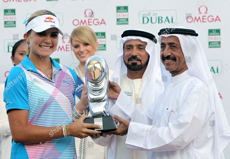 Stock Photo of Us Golfer Alexis Thompson (l) Receives Her Trophy From H H Sheikh Hasher Bin Maktoum Al Maktoum (r) Director General Dubai Department of Information After Winning the Final Round at Omega Dubai Ladies Masters in Dubai United Arab Emirates 17 December 2011 United Arab Emirates Dubai