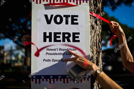 Carol White Hangs a Sign Before the Start of the Hawaii Republican Presidential Caucus in Makiki District Park on 13 March 2012 in Honolulu Usa This is the First Year the State of Hawaii is Using a Caucus to Decide How Its Delegate Votes Are Used United States Honolulu