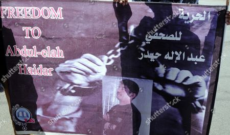 The Shadow of a Yemeni Journalist is Casted on a Banner Showing Imprisoned Journalist Abdul-elah Haidar Shaya During a Protest Demanding His Release in Sana'a Yemen 11 February 2012 According to Media Reports Yemeni Journalist Abdul-elah Haidar Shaya is Imprisoned in a Yemeni Prison Since 2010 After He was Accused of Working For the Interest of the Al-qaeda in the Arabian Peninsula and Conducting Exclusive Interviews with Us-born Critic Anwar Al-awlaki and the Leader of the Yemen-based Al-qaeda Wing Nasser Al-waihashi Yemen Sana'a