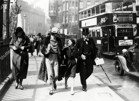 Stock Image of Clementine Churchill and Her Husband Winston Walk Hand in Hand Down A London Street with Their Youngest Daughter Mary (later Baroness Soames) They Are On Their Way to Westminster Hall For A Ceremony in Which Their Majesties King George V and Queen Mary Will Receive an Address of Congratulation From Each House of Parliament 9th May 1935 9th May 1935