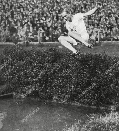 400 Metres Hurdles Gold Medallist Lord Burghley at the Water Jump in the Steeplechase at an Athletics Meeting at Stamford Bridge Shortly After His Win at the 1928 Amsterdam Olympic Games David George Brownlow Cecil 6th Marquess of Exeter (1905 - 1981) Lord Burghley Was an Athlete Sports Official and Conservative Party Politician As an Athlete Burghley Was A Very Keen Practitioner Who Placed Matchboxes On Hurdles and Practised Knocking Over the Matchboxes with His Lead Foot Without Touching the Hurdle in 1927 His Final Year at Magdalene College Cambridge He Amazed Colleagues by Sprinting Around the Great Court at Trinity College in the Time It Took the College Clock to Toll 12 O'clock Inspiring the Scene in the Film Chariots of Fire (whose Character Lord Andrew Lindsay is Based Upon Burghley) in Which Harold Abrahams Accomplishes the Same Feat Lord Burghley Did not Allow His Name to Be Used in the Film Because of the Inaccurate Historical Depiction in the Movie There Was Never A Race Upon Which Harold Abrahams Beat Lord Burghley in This Feat As the Movie Depicts Burghley is Also Said to Have Set Another Unusual Record by Racing Around the Upper Promenade Deck of the Queen Mary in 57 Seconds Dressed in Everyday Clothes Burghley Later Served As President of the Amateur Athletic Association For 40 Years President of the International Amateur Athletic Federation For 30 Years and As A Member of the International Olympic Committee For 48 Years He Was Also Chairman of the Organising Committee of the 1948 Summer Olympics 1928