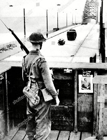 Photograph Showing Aan Irish Guardsman Keeping Watch On the Bridge at Nijmegen September 1944 On 17th September 1944 Operation 'Market Garden' Was Put Into Action; A Bold Plan Devised by Field-marshal Montgomery to Drop Thousands of Airborne Troops Into Holland to Capture an Invasion Route Into Germany the British First Airborne American 81st and 101st Divisions Took Part in the Plan Which Was Ultimately Unsuccessful This Photographed Was Staged (for the Illustrated London News) and the Soldier is James Lawler of the 1st Battalion Irish Guards the Sentry Box Was Previously Manned by Germans and A Picture of Hitler Can Be Seen Still Pinned to the Side of the Wooden Position Apparently the Iln Correspondent Had to Be Encouraged to Make the High Ascent to the Box by Ladder As He Was Scared of Heights!! 1944