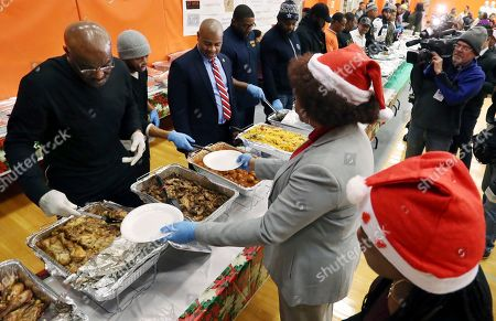 """Delroy Lindo, Ras Baraka Actor Delroy Lindo, left, joined Newark Mayor Ras Baraka, third left, as they helped serve food at a Newark's Weequahic High School high school during an event to feed residents as part of a program to bring holiday cheer, in Newark, N.J. The London-born Lindo's lengthy film career includes roles in movies such as """"Crooklyn,"""" """"Malcolm X"""" and the TV series """"Blood and Oil"""" and """"The Chicago Code"""