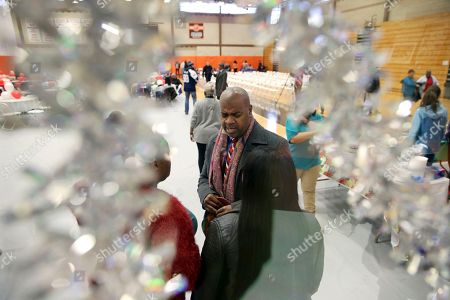 Newark Mayor Ras Baraka, center, is seen through Christmas decorations as he greets people at a Newark's Weequahic High School high school at an event to feed residents as part of a program to bring holiday cheer, in Newark, N.J. London-born actor Delroy Lindo joined Baraka