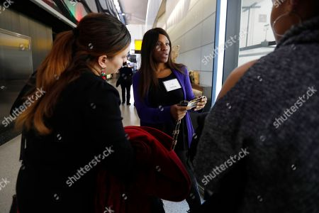 Barbara Murray, center, talks to potential customers at a jewelry kiosk at Newark Liberty International Airport in Newark, N.J. The kiosk, which is in operation until the end of the month, features jewelry produced by former inmates through a society re-entry program by former New Jersey Gov. Jim McGreevey