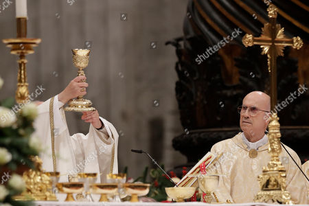 Cardinal Tarcisio Bertone, right, looks at Pope Francis holding up a calix during the Christmas Eve Mass celebrated in St. Peter's Basilica at the Vatican