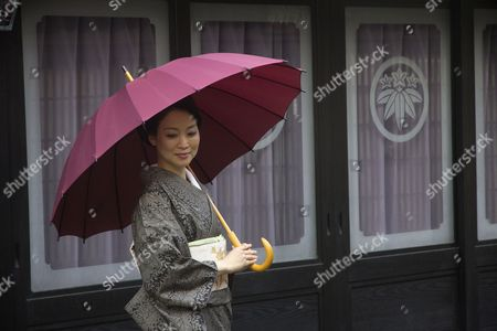 Stock Photo of In this photo released 25 December 2016 is seen a Japanese woman wearing a kimono at Tomonoura port in Fukuyama city, Hiroshima prefecture, 23 December 2016. The port of Fukuyama is known for its traditional architecture and as the setting for the film Ponyo, by Japanese film director Hayao Miyazaki.