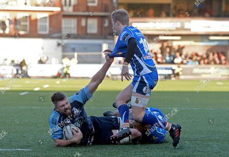 Cardiff Blues vs Newport Gwent Dragons. Cardiff Blues' James Down is tackled by Ashton Hewitt and Angus O'Brien Dragons