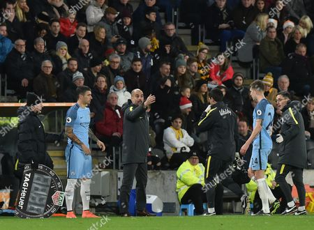 John Stones of Manchester City goes off injured as Aleksander Kolarov of Manchester City comes on with Manager Josep Guardiola of Manchester City looking on during the Premier League match between Hull City and Manchester City played at The KCOM Stadium,  Hull on Monday the 26th of December 2016