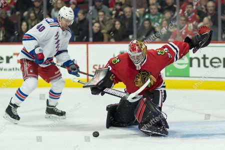 Chicago, Illinois, U.S. - Blackhawk #33 Goaltender Scott Darling stops a shot by Ranger #40 Michael Grabner during the National Hockey League game between the Chicago Blackhawks and the New York Rangers at the United Center in Chicago, IL