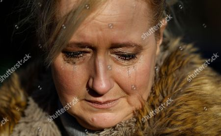 A fan cries outside the home of British musician George Michael in London, . George Michael, who rocketed to stardom with WHAM! and went on to enjoy a long and celebrated solo career lined with controversies, has died, his publicist said Sunday. He was 53