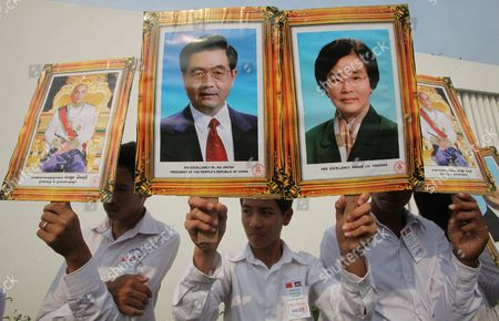 Stock Picture of Cambodian Students Carry Portraits of Chinese President Hu Jintao (c-l) His Wife Liu Yongqing (c-r) and Cambodian King Norodom Sihamoni (l) During a Ceremony at Phnom Penh International Airport Cambodia 30 March 2012 Hu Jintao is on an Official Visit to Cambodia During Which the President Will Meet with Cambodian King Norodom Sihamoni President of the Senate Chea Sim President of the National Assembly Heng Samrin Including Prime Minister Hun Sen Cambodia Phnom Penh