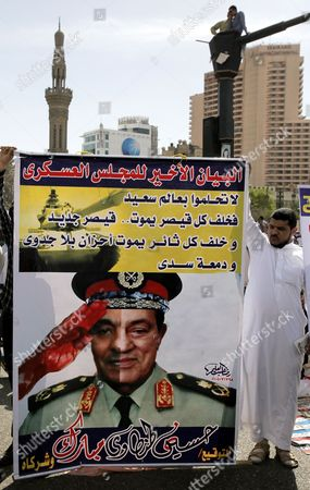 An Egyptian Protester Holds a Banner Depicting Half the Head of the Egyptian Ruling Military Council Mohamed Hussein Tantawi and Half the Former Egyptian President Hosni Mubarak During a Protest Against Presidential Hopefuls with Links to the Mubarak Regime Egypt 13 April 2012 According to Media Reports Thousands of Protesters Staged an Islamist-dominated Demonstration Against Presidential Candidates with Links to the Regime of Former President Hosni Mubarak the Protest is Organized a Day After Egypt's Parliament Now Dominated by Islamists Passed a Law Barring Senior Officials of the Mubaraks Regime From Competing in Next Month's Presidential Election Egypt Cairo