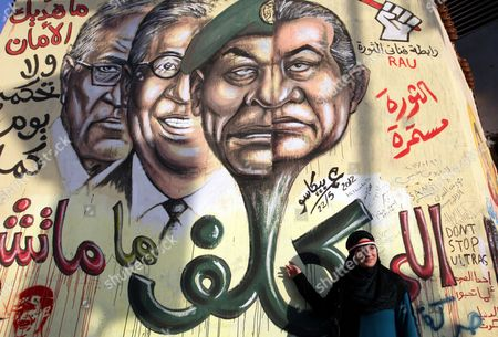 An Egyptian Woman Poses For a Photograph Next to Wall Graffiti Depicting (r to L) Former President Hosni Mubarak Head of the Ruling Military Council Mohamed Hussein Tantawi Former Presidential Candidate Amr Moussa and Presidential Candidate in the Run-off Ahmed Shafiq in Tahrir Square Cairo Egypt 04 June 2012 Opposition Groups Have Called For Mass Protests on 05 June Against the Verdict in the Trial of Mubarak and Security Aides and Against the Candidacy of Ahmed Shafiq Mubarak's Last Premier in the Presidential Election Runoff Egypt Cairo