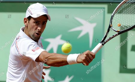 Novak Djokovic of Serbia Returns to Potito Starace of Italy During Their First Round Match For the French Open Tennis Tournament at Roland Garros in Paris France 28 May 2012 France Paris