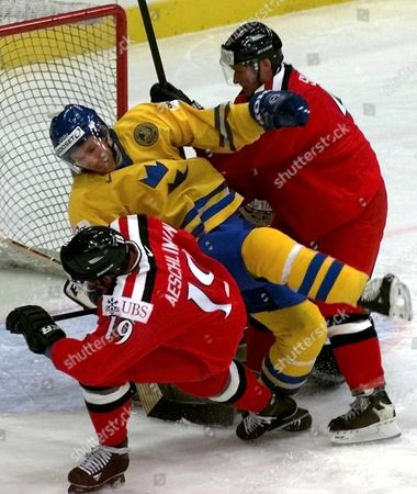 St Petersburg Russian Federation : Swiss Players Jean-jacque Aeschlimann (l) and Patrik Sutter (r) Fight For the Puck with Swede Peter Nordstrom (c) During the Qualifying Match at the Ice Hockey World Championship in St Petersburg Saturday 06 May 2000