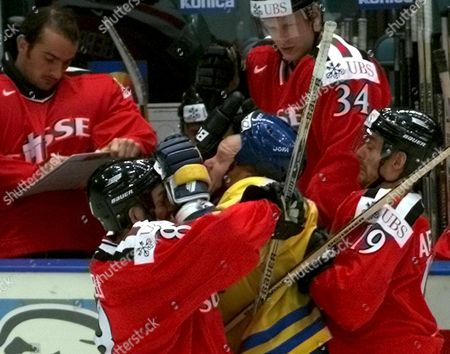 St Petersburg Russian Federation : Swiss Players Claudio Micheli (l) and Jean-jacque Aeschlimann Attack Swedish Peter Andersson (c) During Their Qualifying Match at the Ice Hockey World Championship in St Petersburg Saturday 06 May 2000 the Score After the Game is 1-1