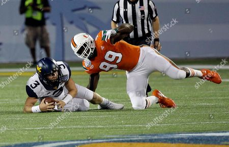 Stock Image of Miami defensive lineman Joe Jackson (99) sacks West Virginia quarterback Skyler Howard (3) during the first half of the Russell Athletic Bowl NCAA college football game, in Orlando, Fla